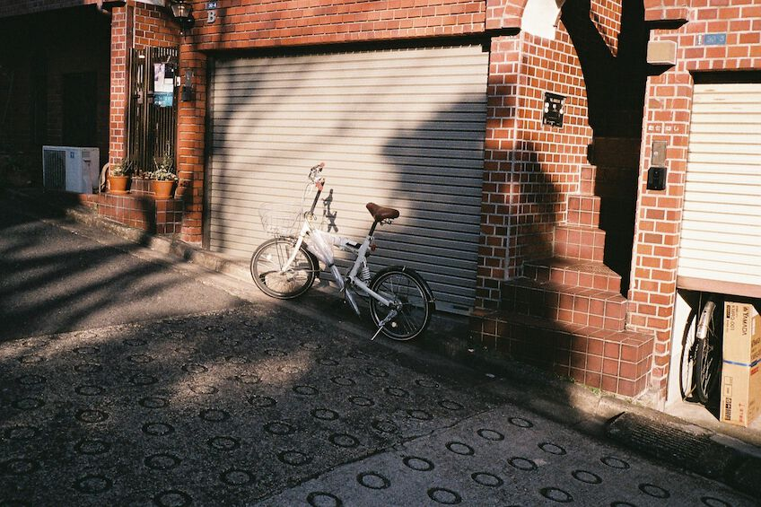 White bike in front of a garage