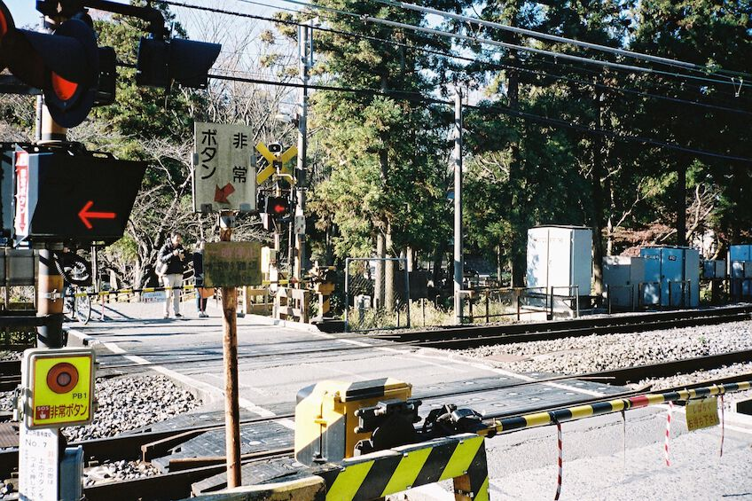 Closed rail crossing with pedestrians waiting on the other side