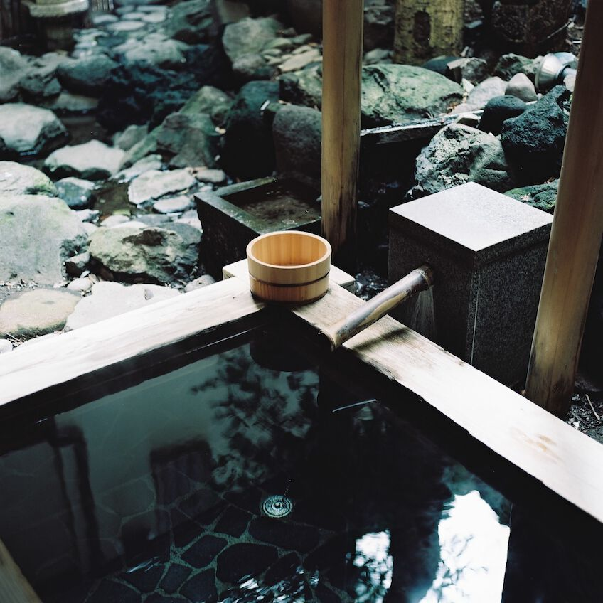 Tiny wooden bath filled with water reflecting the surroundings