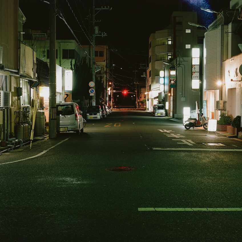 Empty street in Fukuoka with a red traffic light in the distance