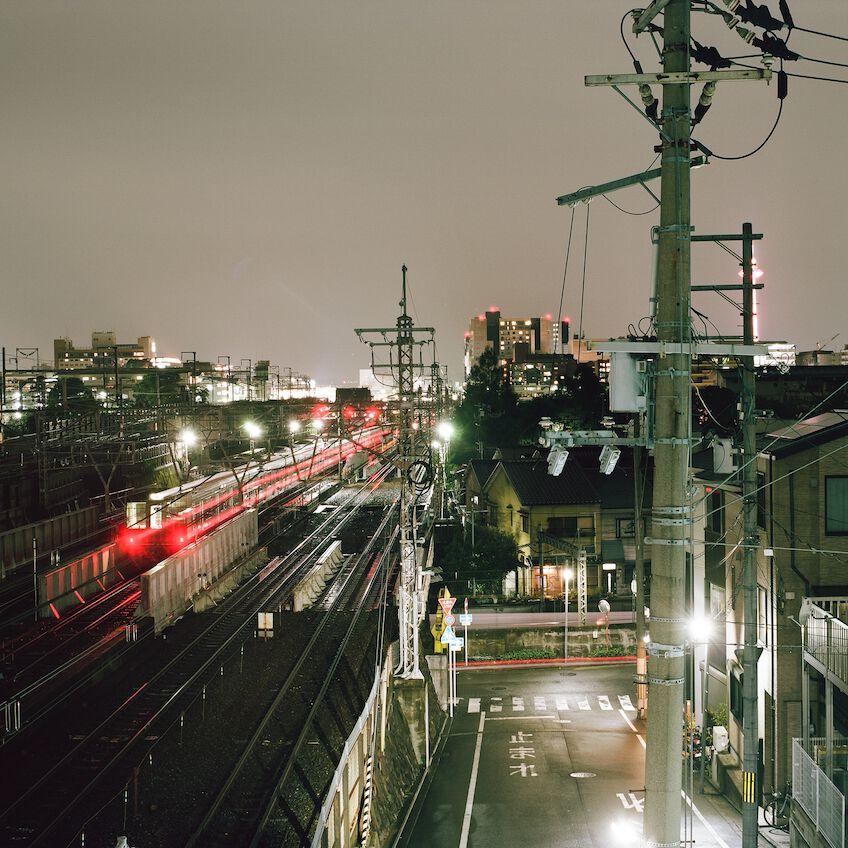 Train tracks in Kyoto with a train passing by
