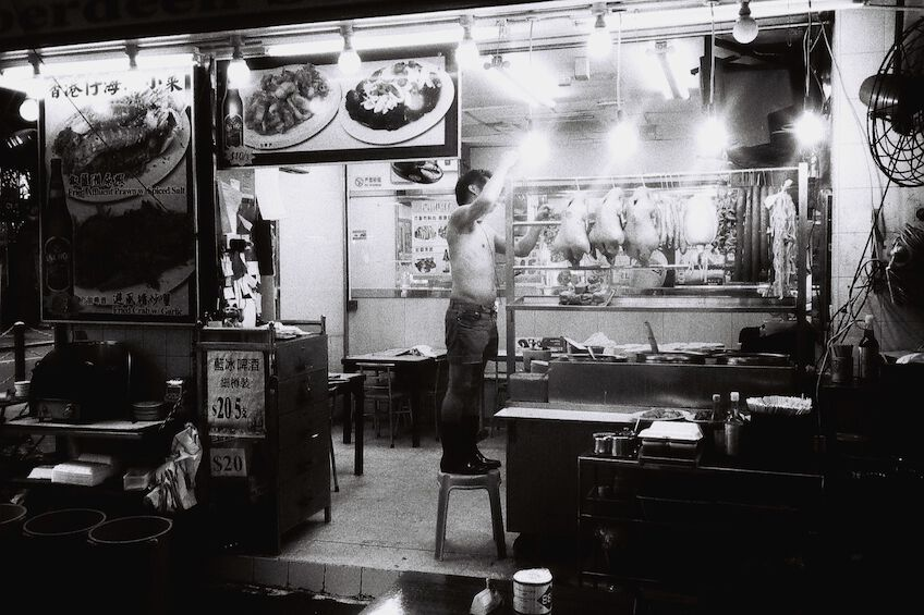 Shirtless man on a stool in a restaurant
