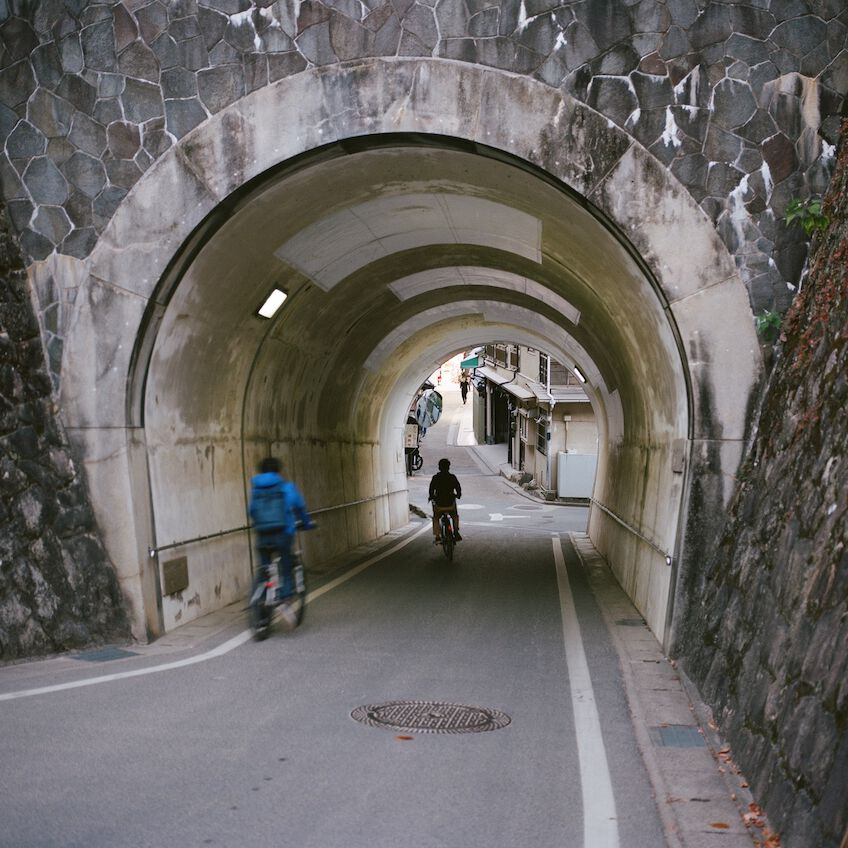 Two kids biking through a tunnel