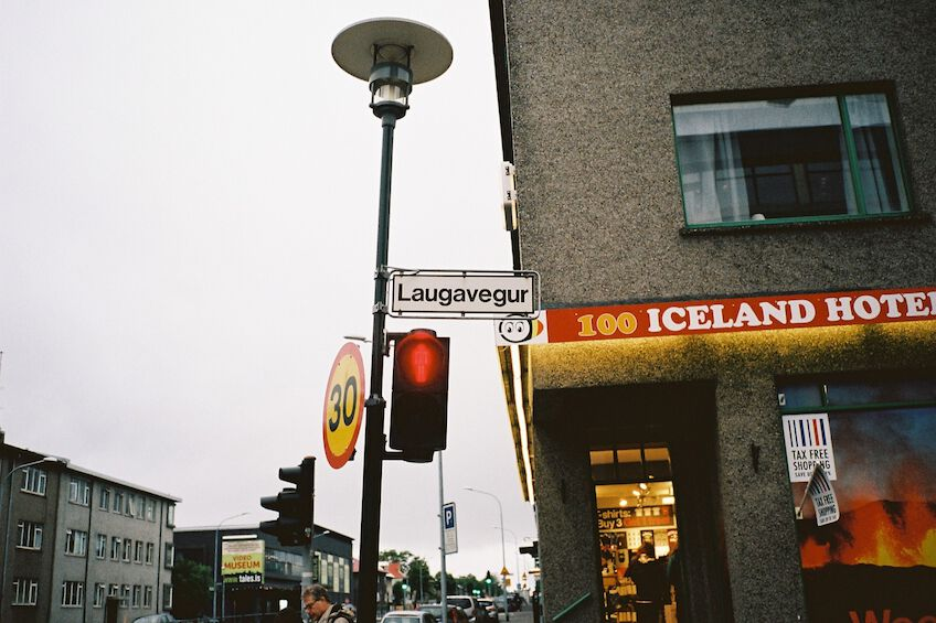 Sign for the street Laugavegur with 100 Iceland Hotel in the background