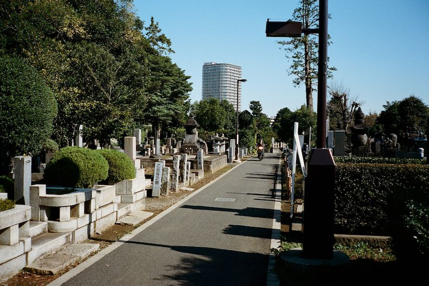 Man on a motorbike driving through Yanaka cemetary